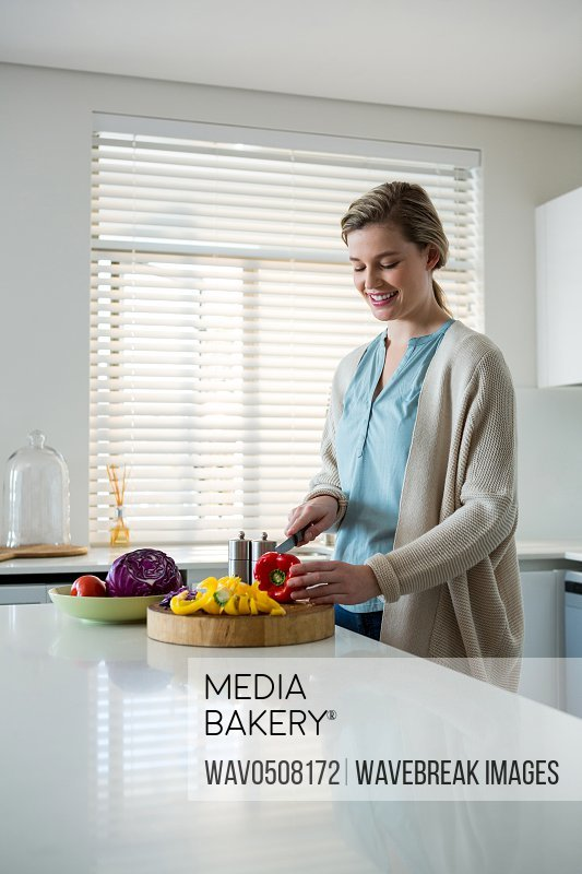 Woman cutting vegetables in kitchen at home