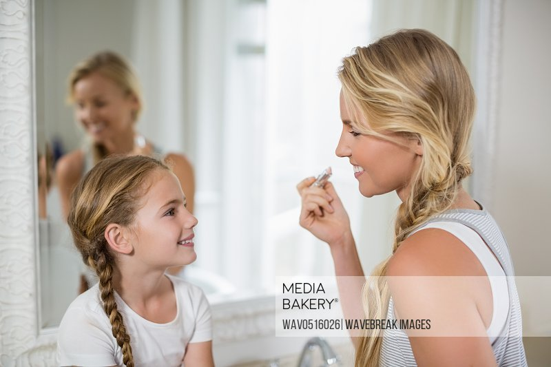 Mother interacting with daughter while applying a lipstick in bathroom