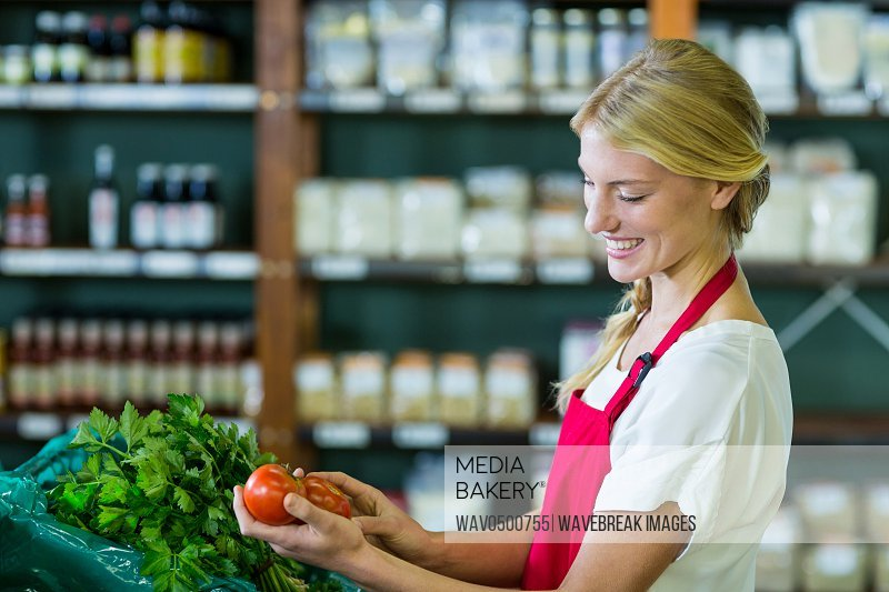 Smiling female staff checking vegetables in organic section of supermarket