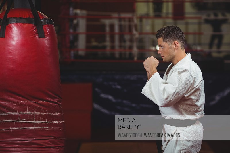 Karate player practicing on punching bag in fitness studio