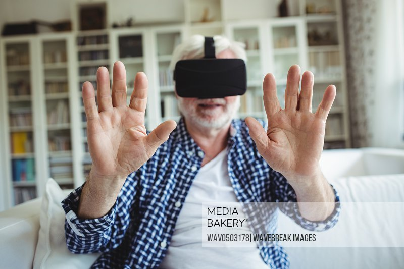 Senior man wearing virtual reality headset in living room at home