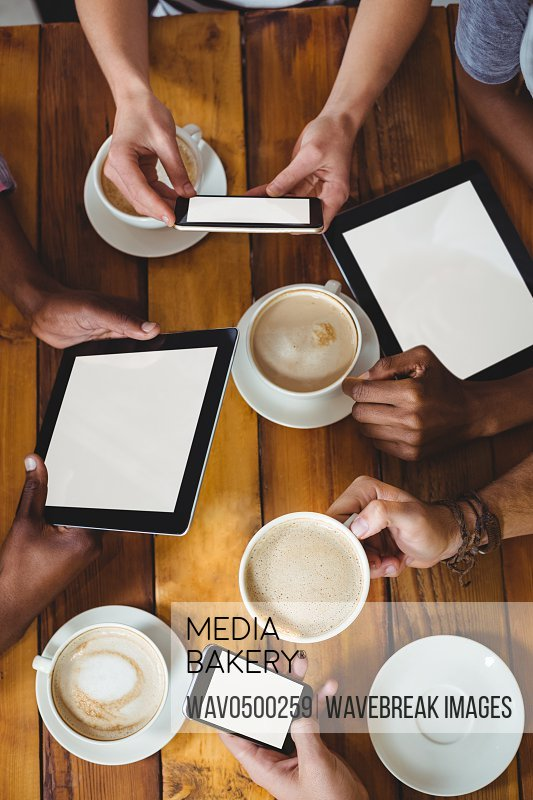 Group of friends using mobile phone while having cup of coffee in cafe