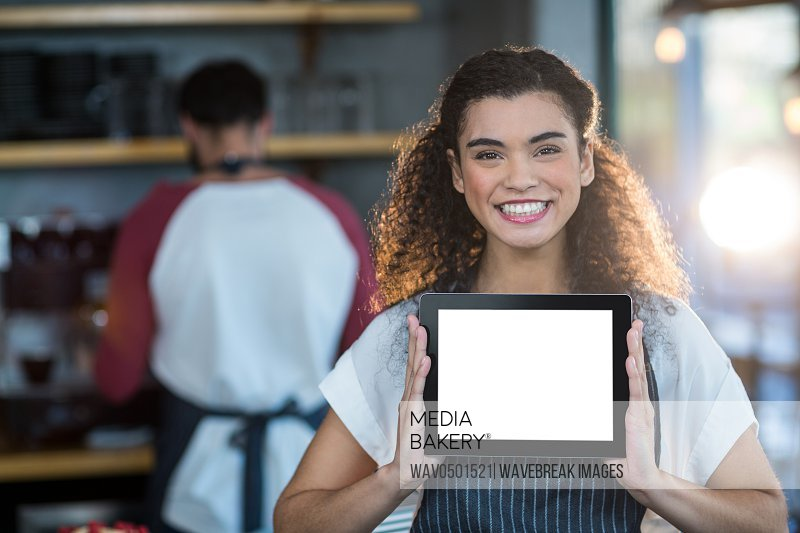 Portrait of smiling waitress showing digital tablet at counter in cafA?