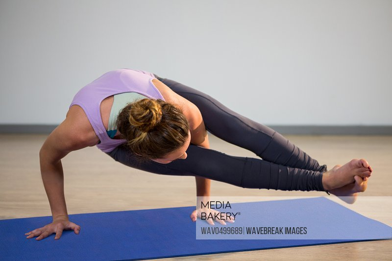 Woman doing eight angle pose on exercise mat in fitness studio