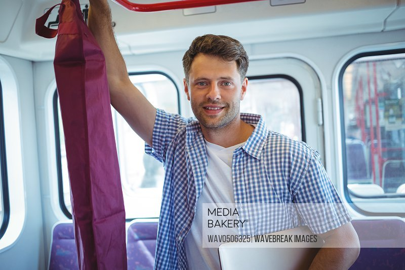 Portrait of handsome man holding laptop while travelling in train