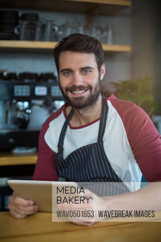 Portrait of smiling waiter using digital tablet at counter in cafe