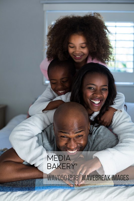 Happy family lying on top of each other on bed at home