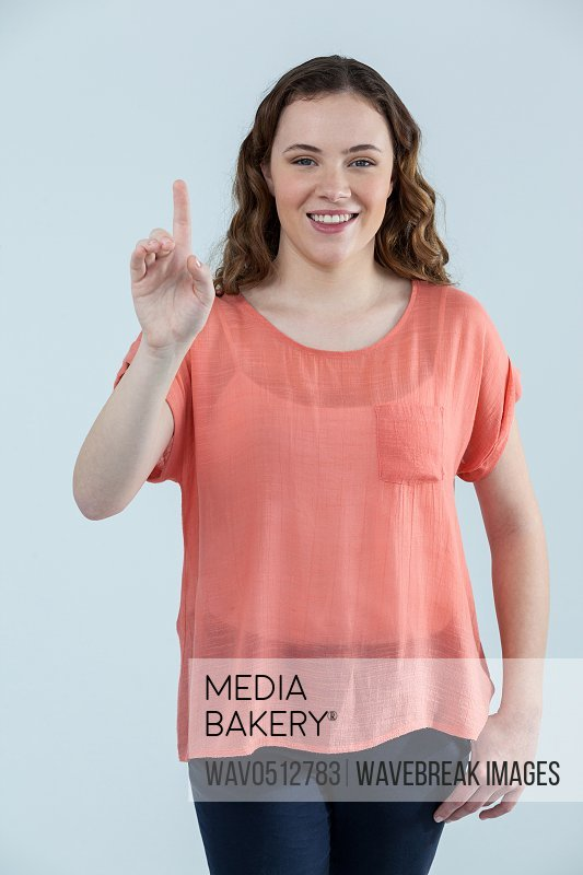 Portrait of woman pretending to touch an invisible screen against grey background