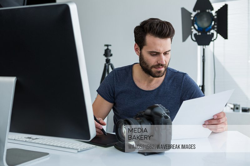 Photographer using graphic tablet at desk