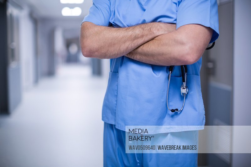 Mid section of male surgeon standing with arms crossed at hospital