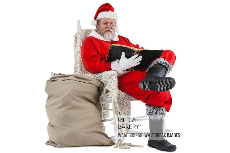 Santa claus reading bible with sack of christmas present beside him