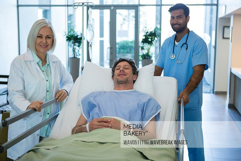 Portrait of doctors standing while patient lying on emergency stretcher in hospital