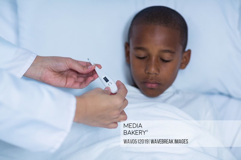 Female doctor checking fever from digital thermometer in hospital