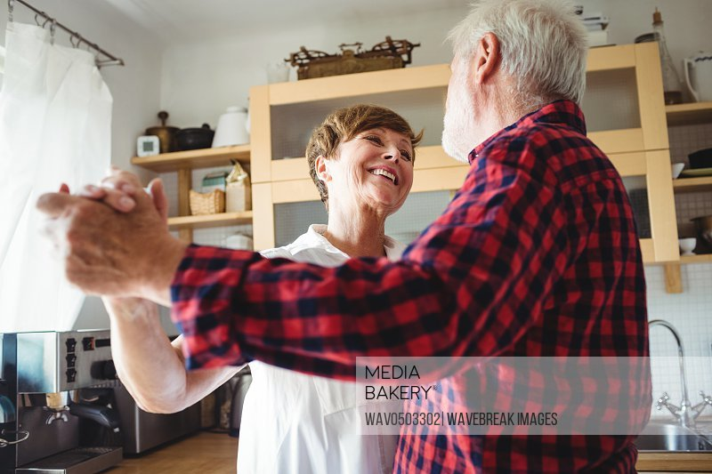Senior couple dancing together in kitchen