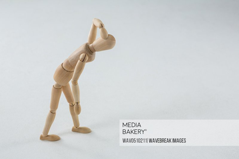 Injured figurine with hand on head against white background