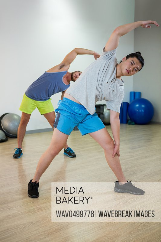 Two men doing aerobic exercise in fitness studio