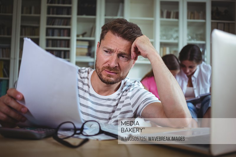 Worried man calculating bills while his wife and daughter sitting on sofa in living room