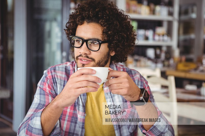 Thoughtful man having coffee in cafeteria