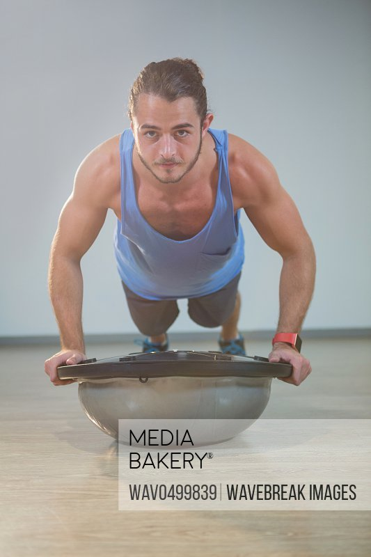 Portrait of handsome man doing push-up on bosuball in gym