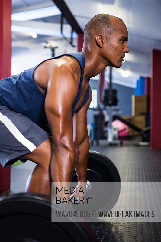 Side view of male athlete lifting barbell in fitness studio