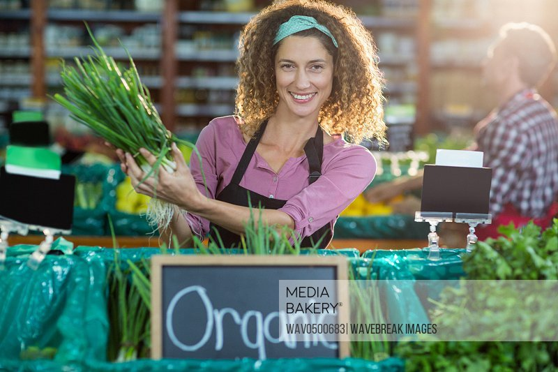 Portrait of smiling staff holding vegetable in organic section of supermarket