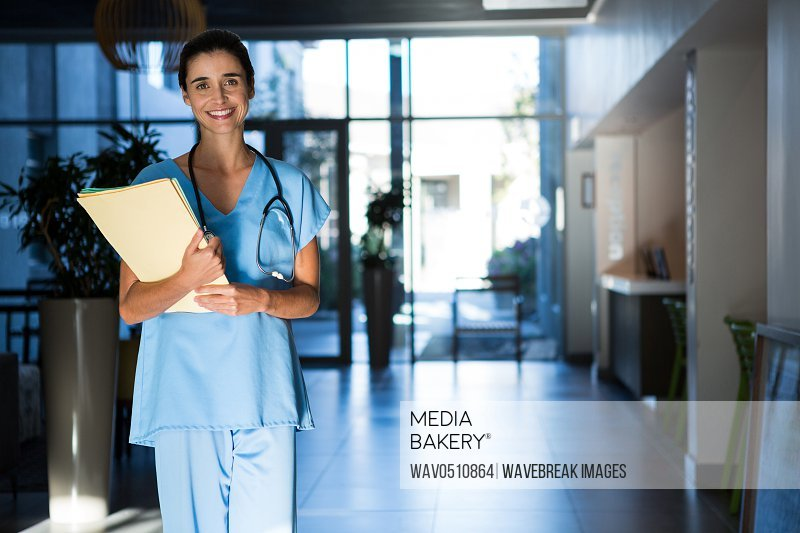 Portrait of female surgeon standing with files in hospital