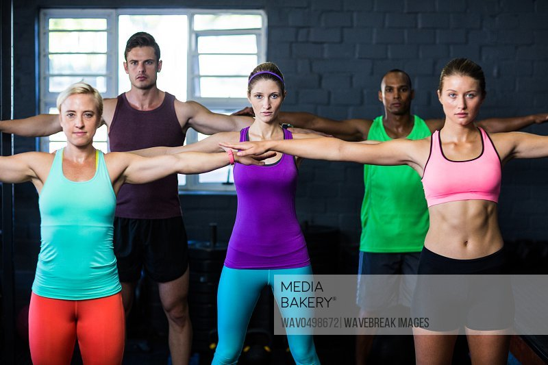 Portrait of young determined athletes exercising in gym
