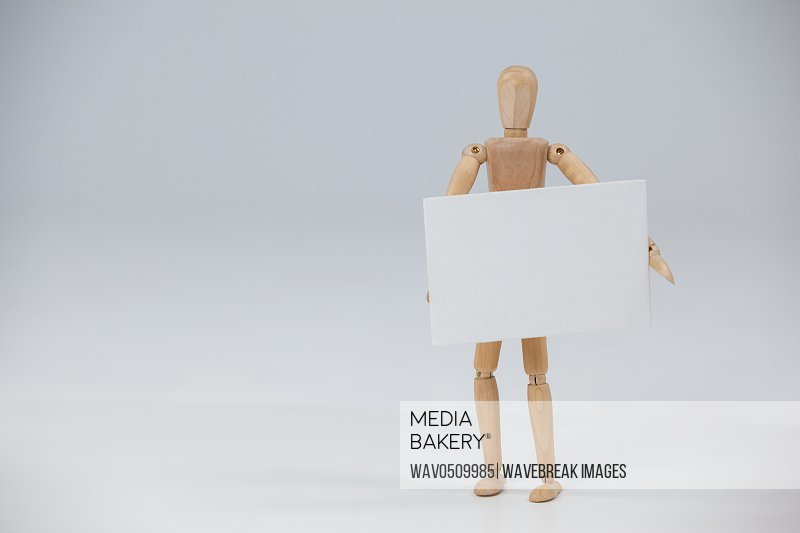 Wooden figurine standing and holding a white placard against white background