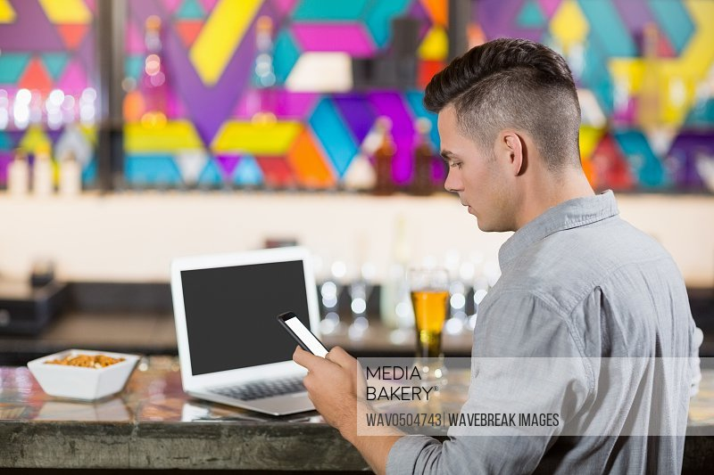 Man using mobile phone with laptop on table at bar counter in bar