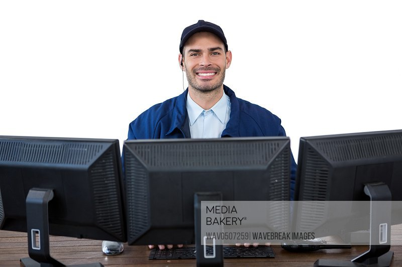 Portrait of happy security officer using computer against white background