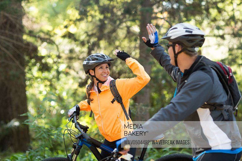 Biker couple giving high five while riding bicycle in the forest at countryside
