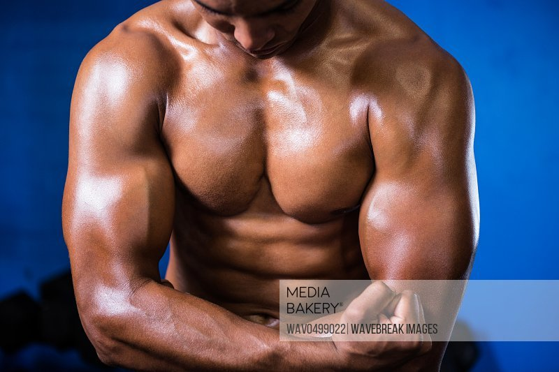 Midsection of muscular shirtless man in gym