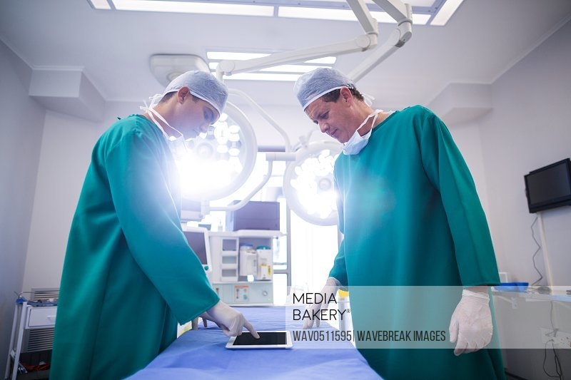 Surgeons using digital tablet in operation theater of hospital