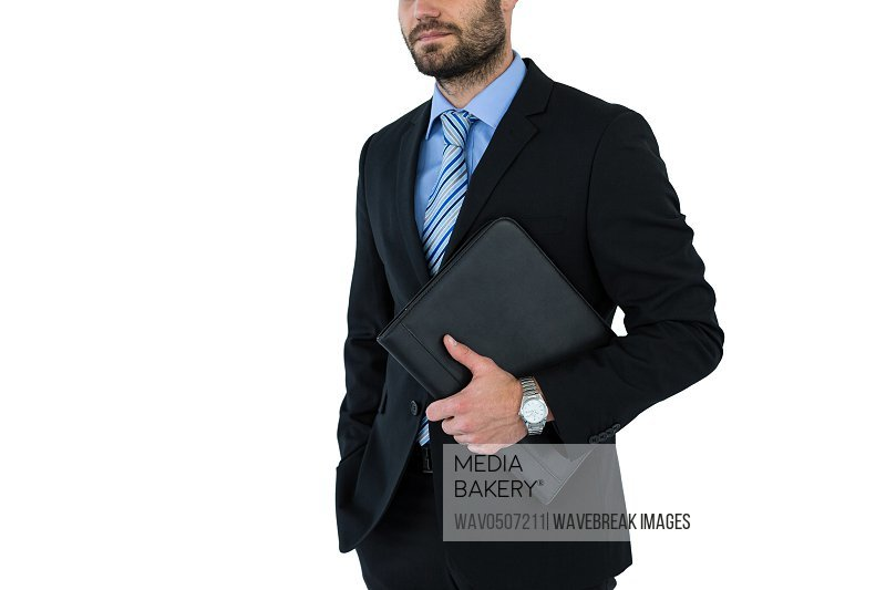 Mid section of businessman holding folder on white background