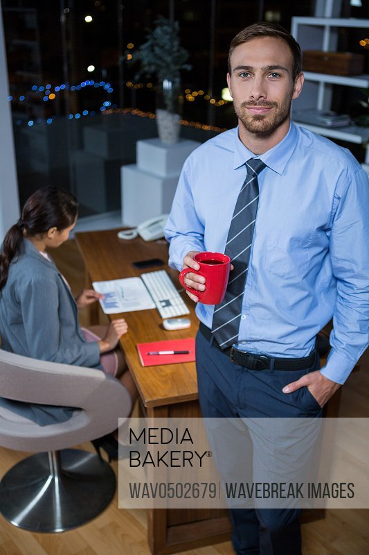 Business executive standing with a cup of coffee in office at night