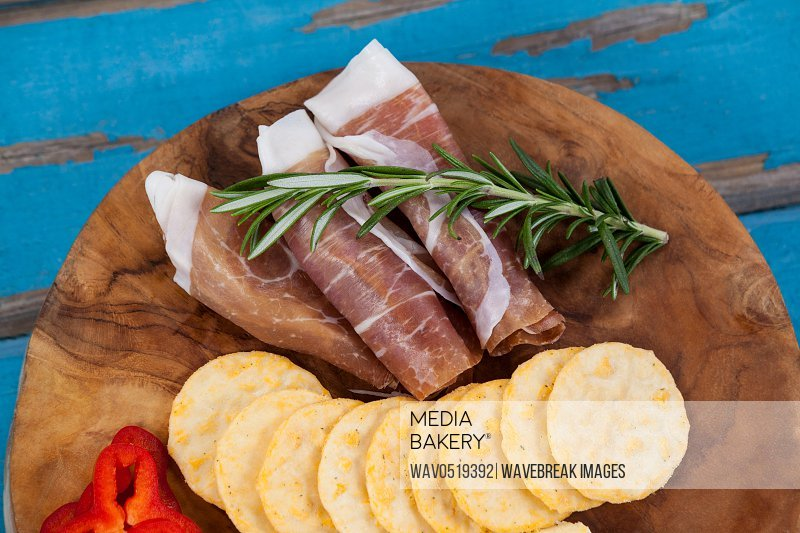 Cheese cubes capsicum meat rosemary and biscuits on wooden board