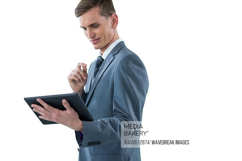 Smiling businessman looking at digital tablet against white background