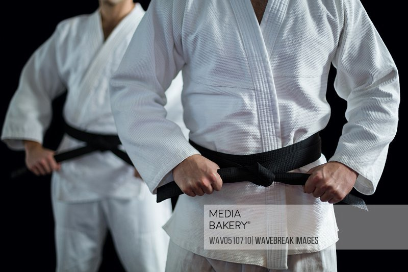 Mid section of Two karate fighters performing karate stance against black background