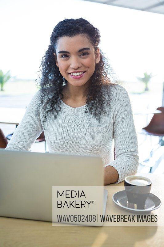 Portrait of smiling woman using laptop and a coffee cup on the table in the coffee shop