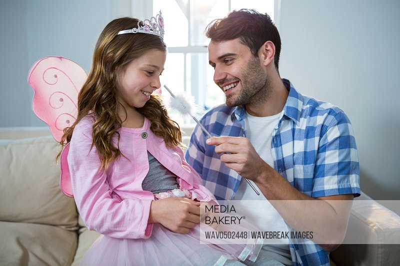 Girl dressed up in a fairy costume interacting with father at home