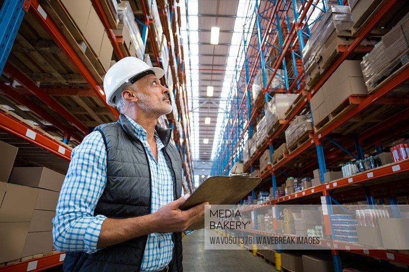 Warehouse worker looking at packages in warehouse