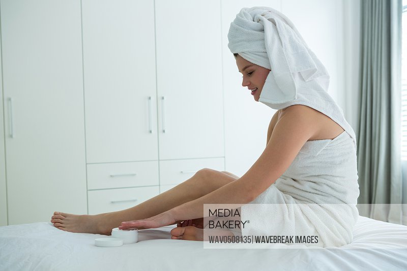 Woman applying moisturizer cream on her leg in bedroom at home