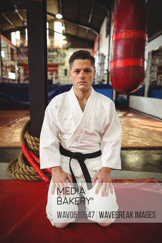 Karate player sitting in seiza position in fitness studio