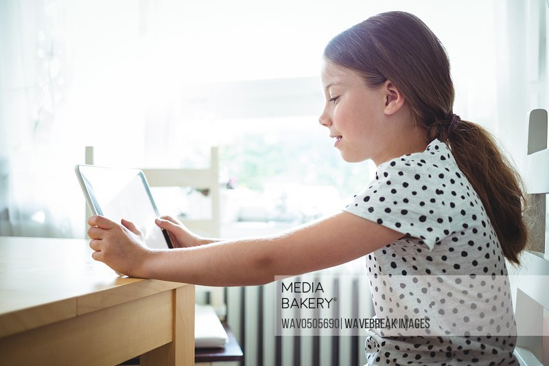 Girl using digital tablet at home
