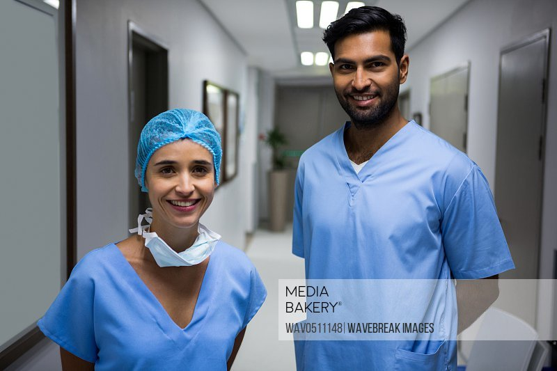 Portrait of smiling surgeons standing in corridor at hospital