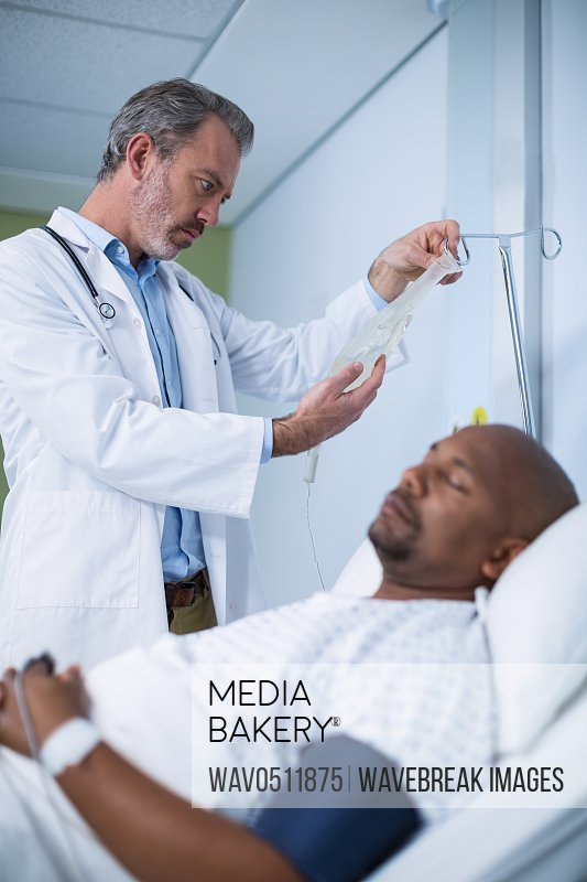 Male patient resting in ward while doctor checking iv drip in background
