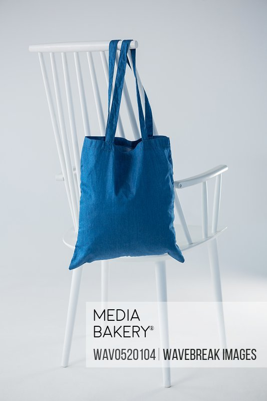Blue bag hanging on a white chair