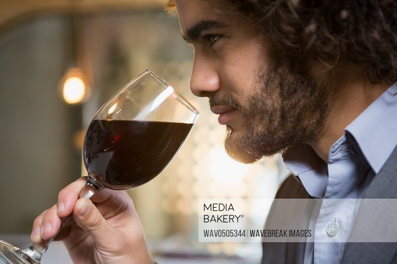 Businessman having glass of red wine in bar