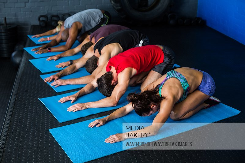 Athletes stretching while kneeling in gym