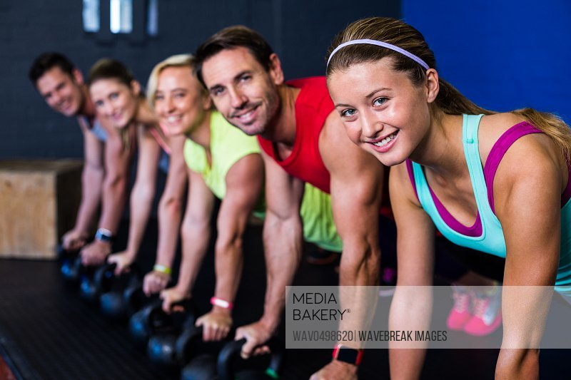 Portrait of smiling male and female athletes exercising with kettlebells in gym